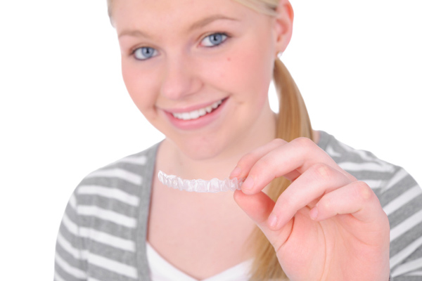 Teenage girl holding her clear aligner from McDonald DDS in Plano, TX