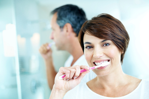 Couple brushing their teeth to prevent tooth sensitivity after visiting McDonald DDS in Plano, TX